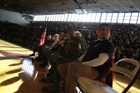 The veterans being honored at the assembly watch a video about the 22 Push-Up Challenge made my Mr. Graham's video class.